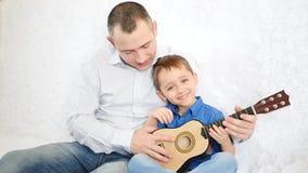 O pai guarda seu filho pequeno e ensina-o que para jogar a guitarra, a criança alegre aplaude a guitarra como se a joga video estoque