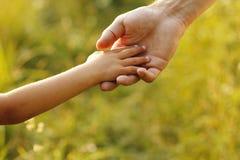 O pai guardara a mão de uma criança pequena Fotografia de Stock