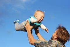 O pai joga acima seu filho no céu, tendo o divertimento Foto de Stock Royalty Free