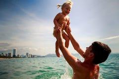 o pai lanç acima de rir a filha pequena acima da água do mar imagens de stock royalty free