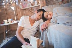 O pai lia contos de fadas registra a seu filho na noite em casa O homem e o menino estão dormindo fotos de stock royalty free