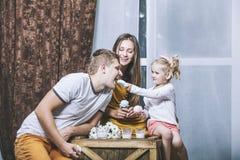 O pai, a mãe e a filha novos bonitos felizes da família bebem m Fotografia de Stock Royalty Free