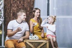 O pai, a mãe e a filha novos bonitos felizes da família bebem m Imagens de Stock Royalty Free
