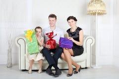 O pai, a mãe e a filha sentam-se com presentes brilhantes Fotografia de Stock Royalty Free