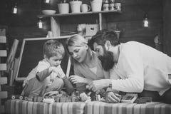 O pai, a mãe e o filho bonito jogam com tijolos do construtor A família na cara ocupada passa o tempo junto na sala de jogos impo fotos de stock