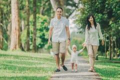 O pai, a mãe e o bebê andam ao longo do parque imagens de stock