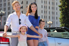 O pai, a matriz e as crianças estão o carro próximo imagem de stock