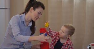 O pai mostra a criança como jogar junto com blocos da construção e ter o tempo do divertimento video estoque