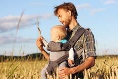 O pai mostra a seu bebê a orelha da cevada Fotos de Stock