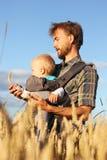 O pai mostra a seu filho a orelha da cevada, quadro vertical, vertical Fotos de Stock Royalty Free