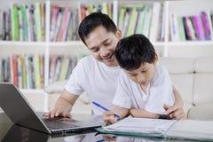 O pai novo ajuda seu filho a estudar na biblioteca imagem de stock royalty free