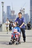 O pai novo empurra um carro de bebê, Shanghai, China Fotos de Stock Royalty Free