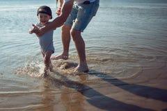 O pai novo ensina o bebê andar homem com uma criança que joga pelo mar foto de stock