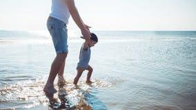 O pai novo ensina o bebê andar homem com uma criança que joga pelo mar fotos de stock
