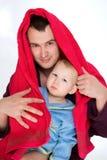 O pai novo feliz com uma criança envolve a toalha Imagens de Stock
