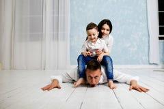 O pai novo tem o divertimento com filha e filho imagem de stock royalty free