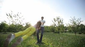 O pai ou o irmão gerenciem a filha ou a irmã no movimento lento do por do sol vídeos de arquivo