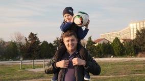 O pai põe seu filho sobre ombros e ajuda-o a jogar acima a bola no movimento lento das portas do futebol vídeos de arquivo