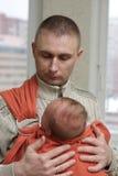 O pai prende seu bebê pelo estilingue Imagem de Stock Royalty Free
