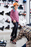 O pai que ajuda ao filho na tentativa sobre patina na loja dos esportes imagens de stock