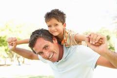O pai que dá o passeio do filho suporta sobre no parque Fotos de Stock