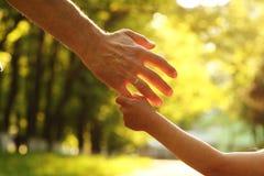 O pai que guarda a mão de uma criança pequena Fotografia de Stock