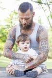 O pai Tattooed tem o divertimento com seu filho Imagens de Stock Royalty Free