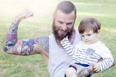 O pai Tattooed tem o divertimento com seu filho Imagens de Stock