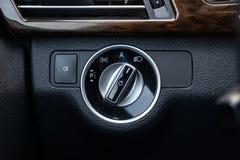 O painel do interior do carro é preto com um interruptor mergulhado do farol e umas luzes laterais com um sensor leve e automátic imagens de stock royalty free
