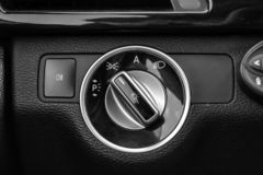 O painel do interior do carro ? preto com um interruptor mergulhado do farol e umas luzes laterais com um sensor leve e autom?tic fotografia de stock