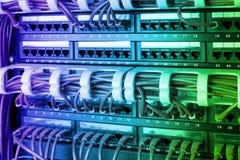 O painel, o interruptor e o Internet da rede cabografam no centro de dados Interruptor preto e cabos ethernet azuis, conceito do  imagens de stock