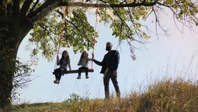 O paizinho agita suas filhas em um balanço sob uma árvore filme