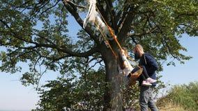 O paizinho agita suas filhas em um balanço sob uma árvore