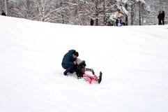 O paizinho ajuda uma criança que caia de um trenó na neve foto de stock