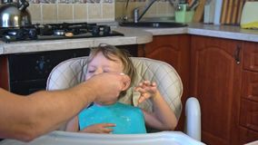O paizinho alimenta o papa de aveia do rapaz pequeno na cozinha filme