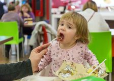 O paizinho alimenta sua filha no café Foto de Stock