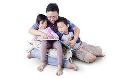 O paizinho com as duas crianças que leem uma história registra Fotografia de Stock Royalty Free