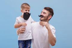 O paizinho com um sorriso olha seu filho ao lado de um fundo azul fotos de stock
