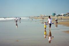 O paizinho com uma criança anda ao longo da praia Fotografia de Stock