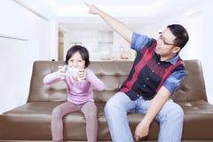 O paizinho dá a ordem em sua filha para parar um jogo Fotografia de Stock Royalty Free
