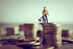 O paizinho diminuto e as crianças que estão sobre o dinheiro salvar o dinheiro c Fotos de Stock Royalty Free
