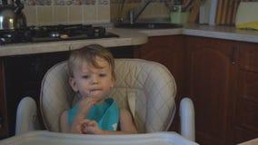 O paizinho do rapaz pequeno alimenta o papa de aveia na cozinha video estoque