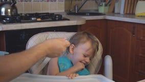 O paizinho do rapaz pequeno alimenta o papa de aveia na cozinha filme