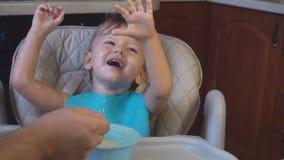 O paizinho do rapaz pequeno alimenta o papa de aveia para o café da manhã filme