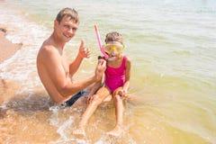 O paizinho e a filha estão considerando o shell subaquático encontrado imagens de stock