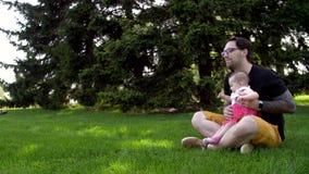 O paizinho e a filha estão sentando-se na grama e estão mostrando-se lhe algo na distância