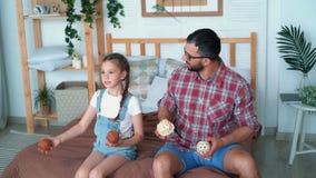 O paizinho e a filha sentam-se na cama e tentam-se manipular com bolas, movimento lento filme