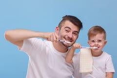 O paizinho e o filho escovam seu close-up dos dentes em um fundo azul imagem de stock royalty free