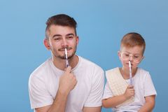 O paizinho e o filho estão guardando escovas perto dos bordos em um fundo azul foto de stock royalty free