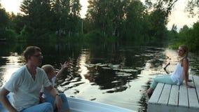 O paizinho e o filho montam em um barco de enfileiramento filme